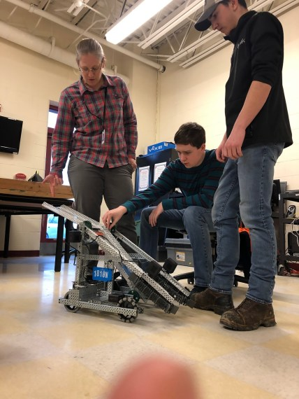 Michelle Lane, Julian Howard, and Dillon Foley discuss improvements to their robot's design.
