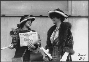 Margaret Foley stands on the right in a fur trimmed hat smiling at the woman on her left who is holding a copy of the Woman's Journal