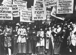 A group of women hold signs advocating for better working conditions