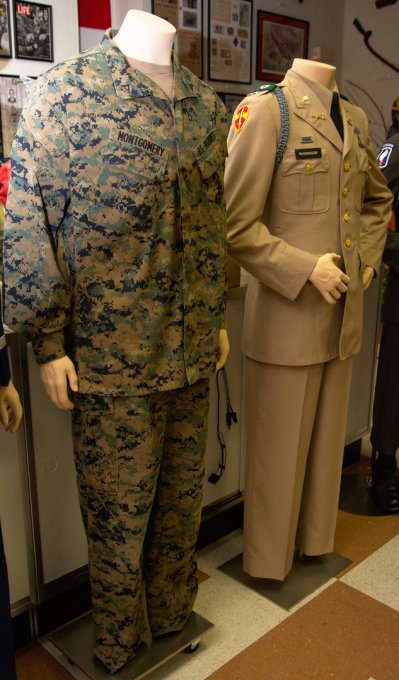 Current combat fatigues for Lance Corporal Sean Montgomery, USMC, currently serving in combat in Afghanistan. On the right are the summer service tans for Captain Jim Mcdonough, US Army, killed in Action in Vietnam on his second tour.