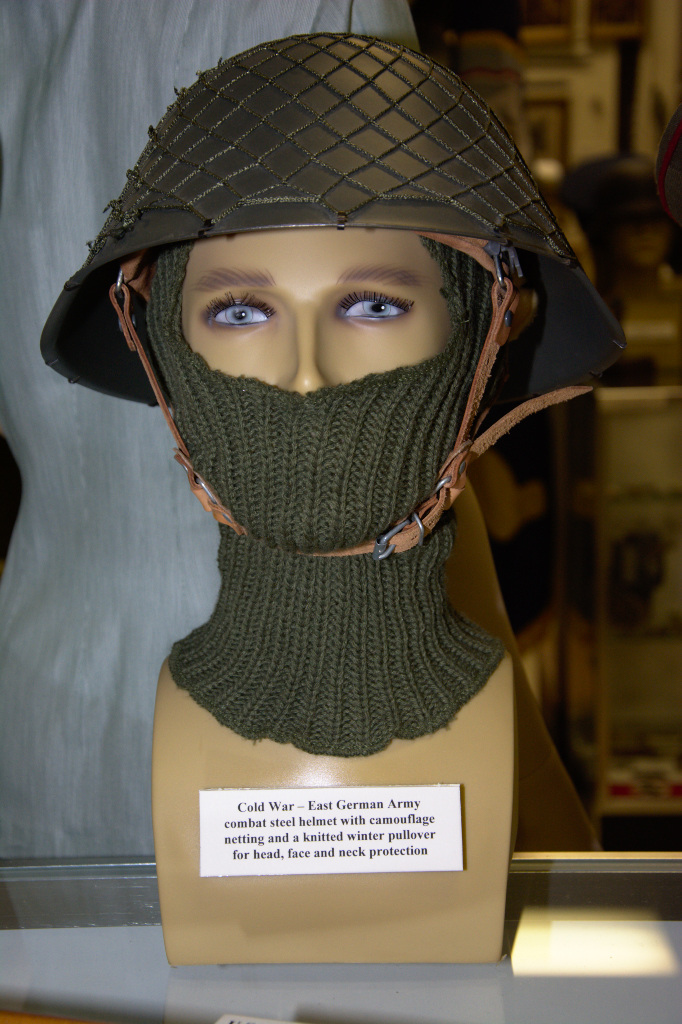 Cold War era East German Army combat steel helmet with camouflage neting and knitted winter pullover.
