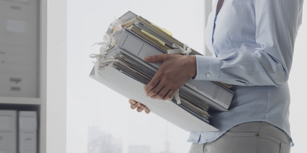Female office worker carrying folders and files in the archive, administration and business concept