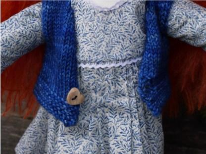 Zoom sur le gilet en laine de la poupée rousse waldorf Anita