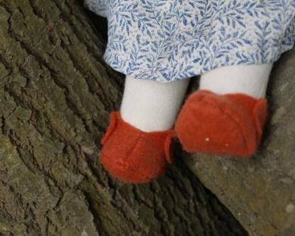 Gros plan sur les chaussons en laine feutrée teinture végétale de la poupée rousse Waldorf