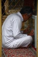 Een soefi (in traditionele witte kleding) bidt bij het graf van Abu Yazid (Bastam)