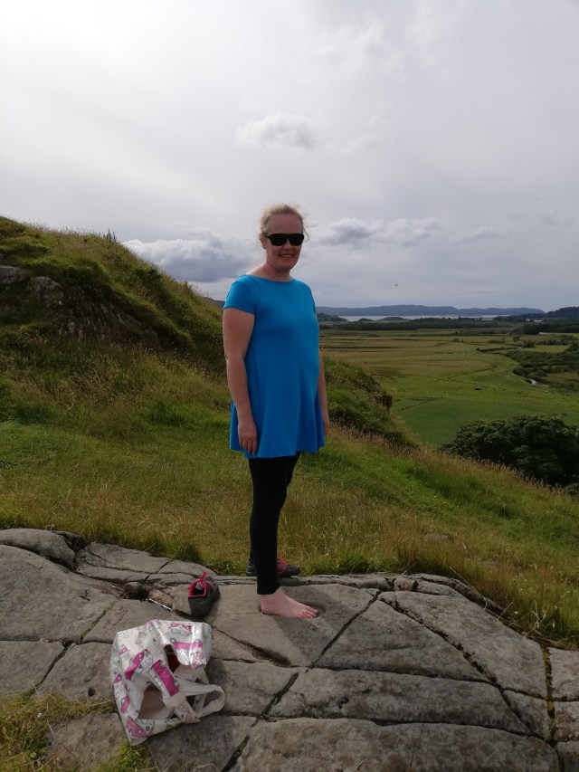 Me standing with my foot in the carved footprint possibly used in the coronation of the kings of DalRiada. The Crinan basin is in the distance behind me.