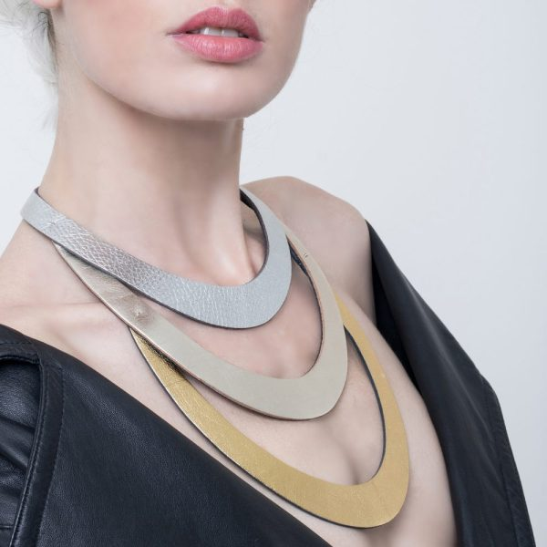 Collar Stripes , collar largo de tres tiras en cuero engamado plateado, dorado claro y dorado oscuro, sobre modelo. Maison Domecq.
