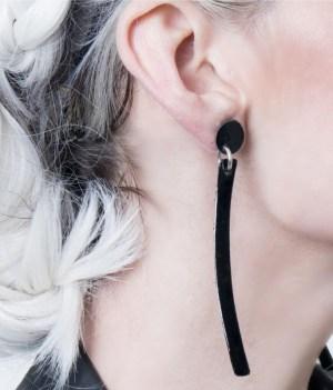 Aros largos Ivi de cuero argentino color negro charol, sobre modelo. Maison Domecq