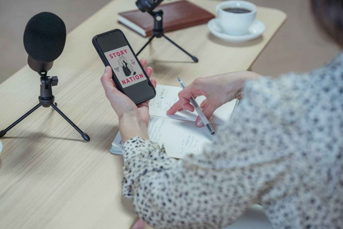 crop unrecognizable woman using smartphone at desk with microphones