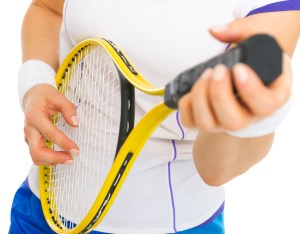 Closeup on female tennis player playing on racket as on guitar