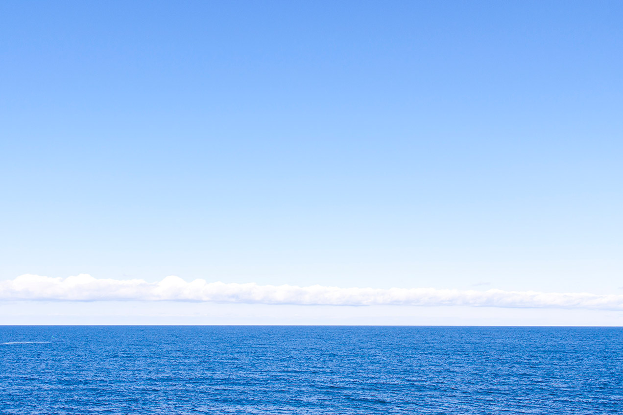 Photo of a calm blue ocean and clouds