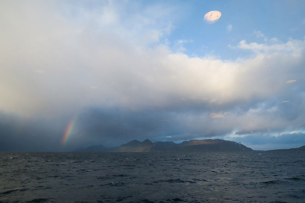 Rainbow over Norwegian fjord and mountains