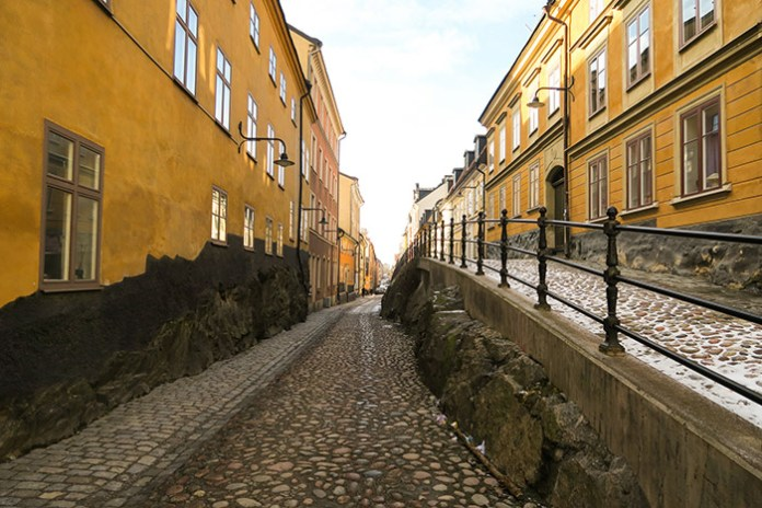 Yellow houses and cobblestone street in Gamla Stan, Stockholm.