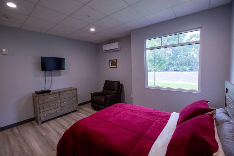 Interior of bedroom with bed, dresser, window, TV