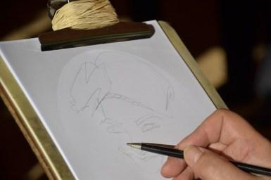 un portraitiste dessine brièvement au crayon la forme du visage, c'est une esquisse