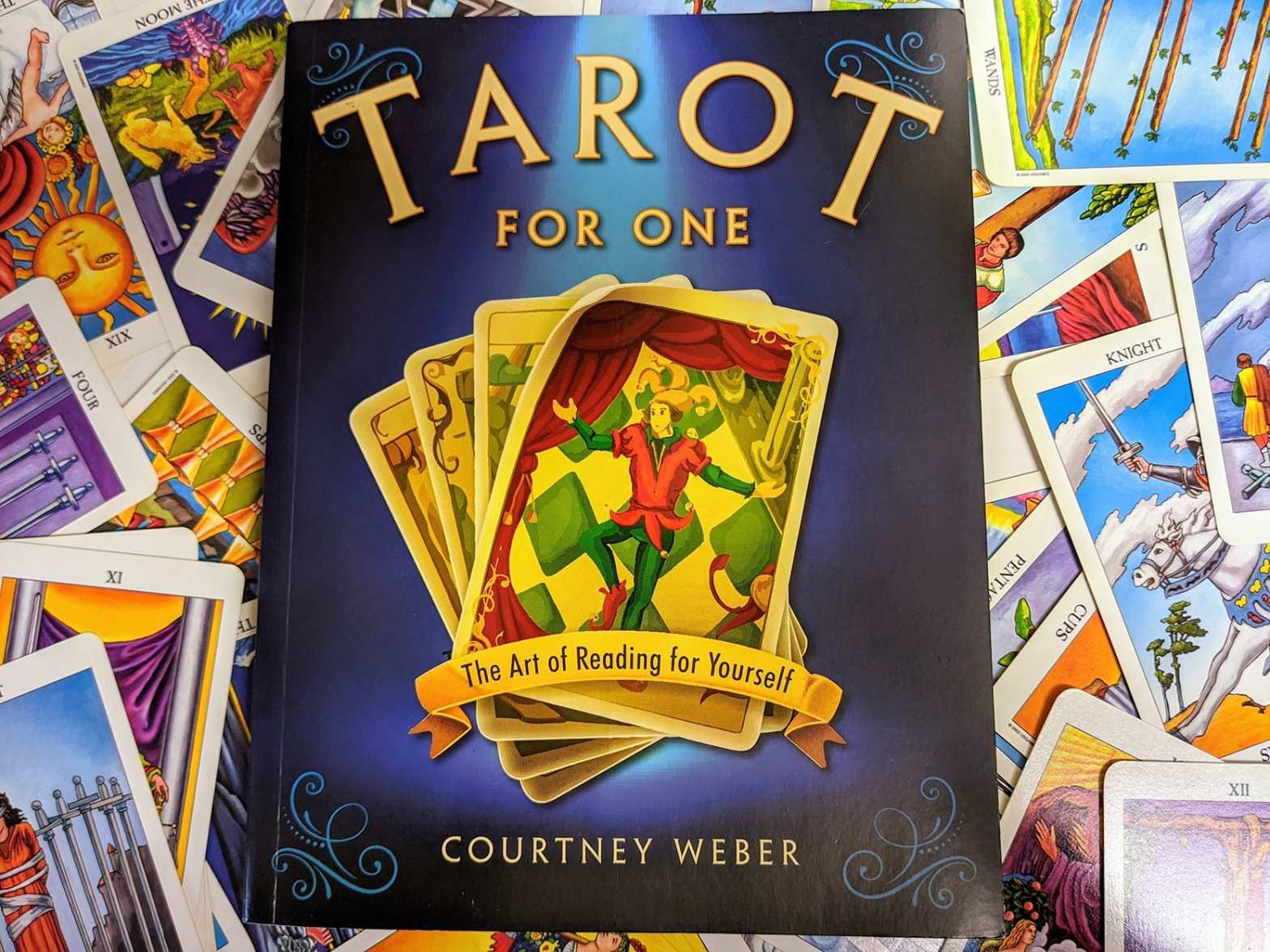 "An image of Courtney Weber's ""Tarot for One"" book set against a scattered pile of Tarot cards"