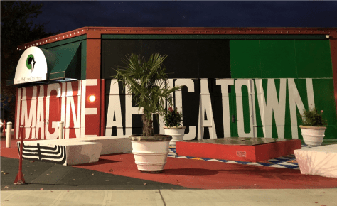 Picture of potted plants and a bench with the word Africatown in the background, painted in bright red and green colors