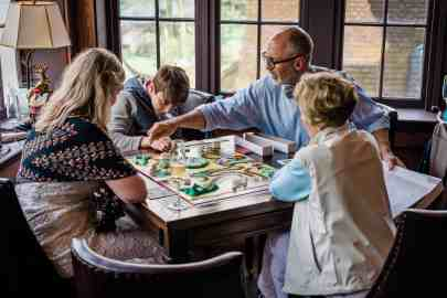 During a casual wedding reception at Greystone Inn, a bride and groom play a board game with family members in the historic Library room.