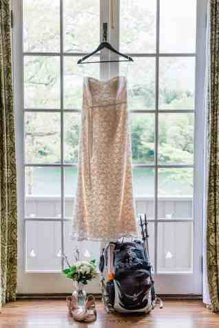 With the waters and trees of Lake Toxaway visible through the glass french doors of a bridal suite at Greystone Inn, a the sun shines through a cream-colored lace wedding dress hanging in the doorway. Set below the dress are a backpack with trekking poles for hiking attached to the side, and the bride's wildflower bouquet and gold colored sandals as the couple readies for their hiking wedding.