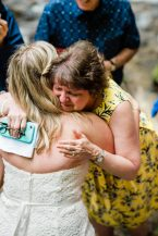 After vow reading in an adventure elopement with family, a mother tearfully hugs the bride