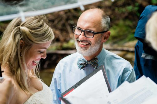 A groom looks at his partner with a huge smile during their hiking elopement ceremony in the rain. They stand together smiling under a clear umbrella.