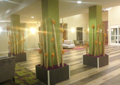 "The Holiday Inn Savannah: Contemporary, high-quality artificial plantscaping on a tight budget. We added purple preserved reindeer moss at the base to create a strong ""pop"" of color, coordinating nicely with the carpeting."