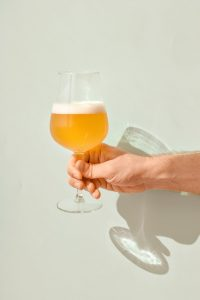 a glass of blonde all grain beer in mans hand