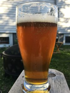 Craft beer in beer glass outside with fire pit in back ground
