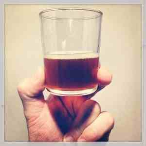 a picture of a hand holding half a glass of beer up in the air