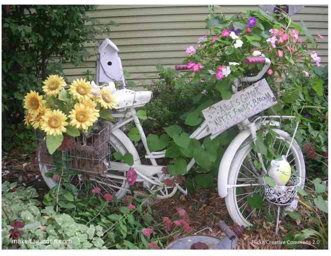 Un vélo vintage pour femme pour décorer votre jardin. Un panier à l'avant et à l'arrière est rempli de fleurs