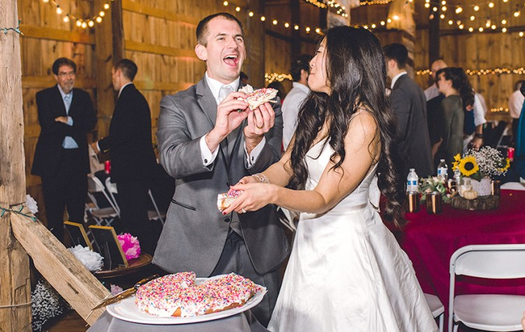 Bride and groom laughing while holding pieces of a giant doughnut