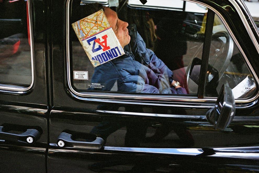 Man resting his head against book in a car