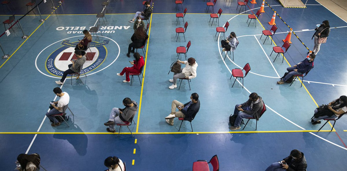 People in a gymnasium sitting in socially distanced chairs