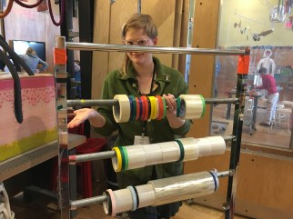 Adult poses behind a metal structure with multiple rods suspending rolls of tape.