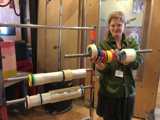 A woman holding a rail of tape apart from the structure of which it was originally a part.
