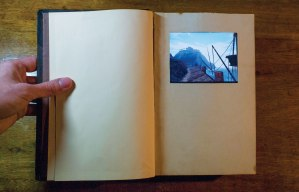 vintage hardcover book open to blank pages with a palm-sized computer touchscreen displaying an image from the computer game Myst of a lonely pier with a misty mountain in the distance