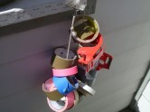 I learned this from my days in film production. Tie a carabiner to a rope, run your tape rolls through, and hang it on a wall. Now they're all easily accessible and won't roll around everywhere.