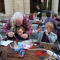 Sam Thompson teaches his young 'uns to solder at the first RI Mini Maker Faire