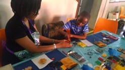 MIT student with the MBADIKA social venture, showing a little boy how to build a solar charging kit.
