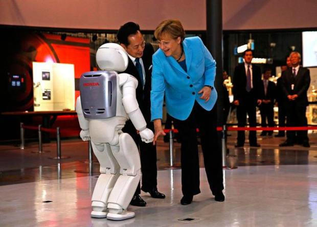 German Chancellor Angela Merkel greets ASIMO along with Mamoru Mohri, executive director for the Miraikan museum in Tokyo.