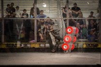 This red-wheeled robot flings the fox wedge robot overhead in its first match.