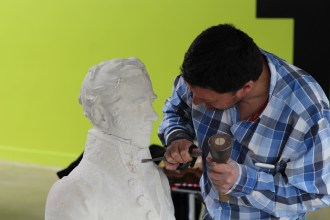 Loïc Maìllard hand carves the finishing touches on a bust originally carved by a robot.