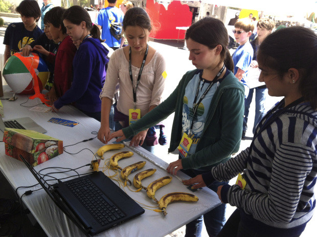 A group of grade school students playing a piano made out of bananas (and a MaKey MaKey). We start 'em thinking outside the box as early as possible.