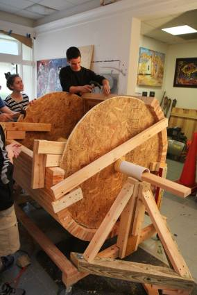 We began by building a rotating form upon which we could attach the wood staves. Each piece was precut by students. The drum form was on wheels so we could move it outside to sand it.