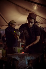 A blacksmith works on her project during Open Forge.