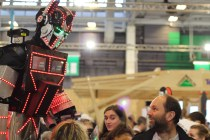 A giant Optimus Prime — illuminated by strips of flashing LEDs — looms over the crowd at Maker Faire Paris.