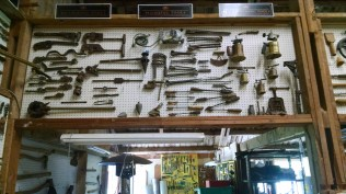 From left to right: measuring, plumbing, and blacksmithing tools