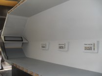 """An interior view of the starboard side. Each seat (not shown here) has a corresponding """"environmental control"""" unit next to it."""