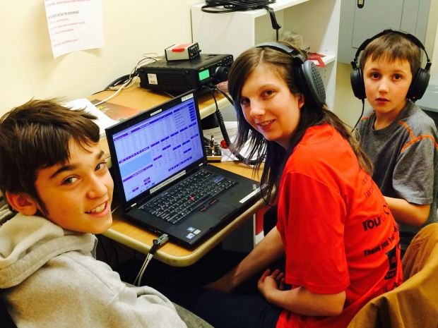 Anna Veal, WØANT, is busy coaching future hams Matthew Harris (left) and Jasper Smith (right).  They were competing in one of the many ham radio contests - ARRL November Sweepstakes - from the Douglas County, Coloradio STEM School and Academy club station whose call sign is ABØBX. (Photo by Byron Veal, NØAH and provided courtesy of the ARRL)