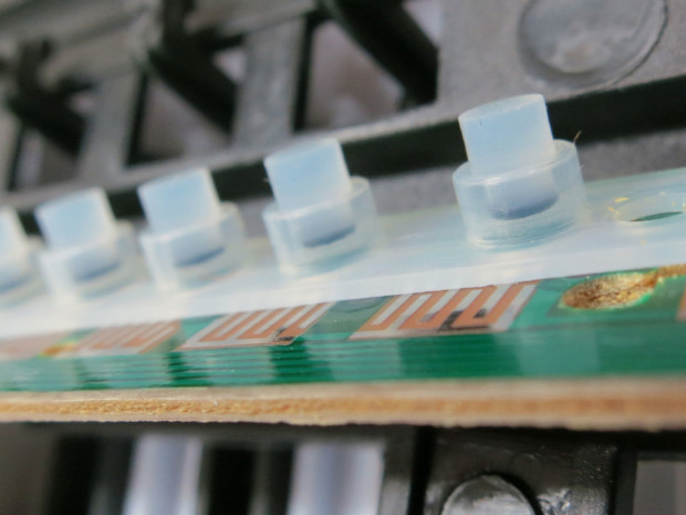 Removing the thin circuit board reveals rubber buttons, such as you would find inside a computer keyboard. These activate the traces underneath.